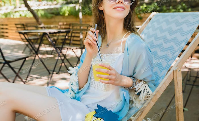 young attractive woman sitting in deck chair in summer fashion outfit