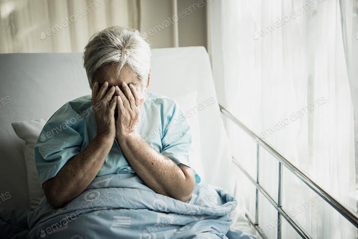 Ältere Patienten sitzen im Bett und warten darauf, dass Verwandte einsam vorbekommen.