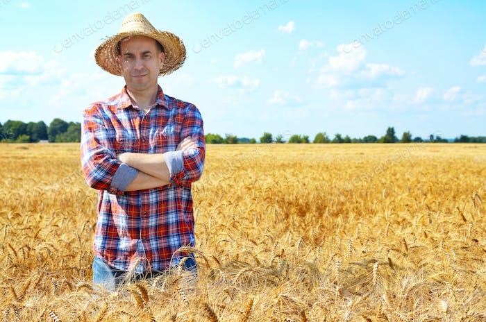 Glücklich aussehende Bauer in Strohhut steht bei der Ernte bereit Weizen