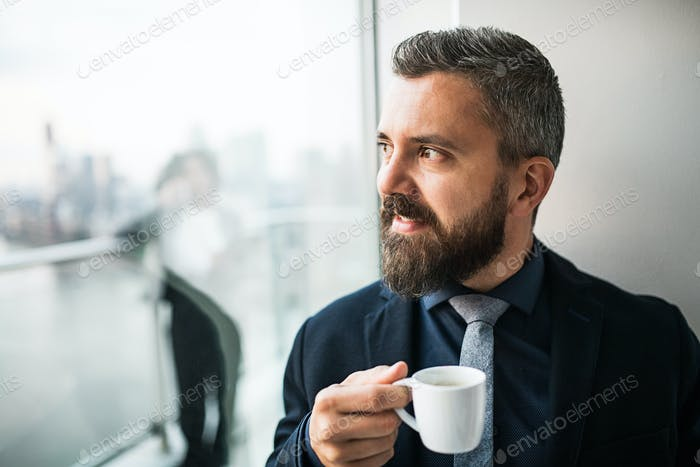 A portrait of businessman with a cup of coffee looking out of a window in an office.
