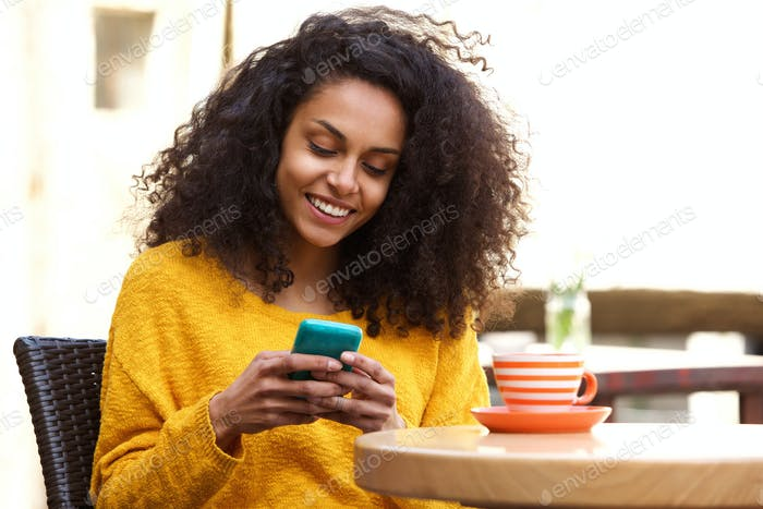 Beautiful african woman using mobile phone at coffee shop