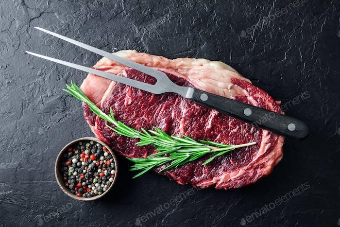 Marbling ribeye steak on black table