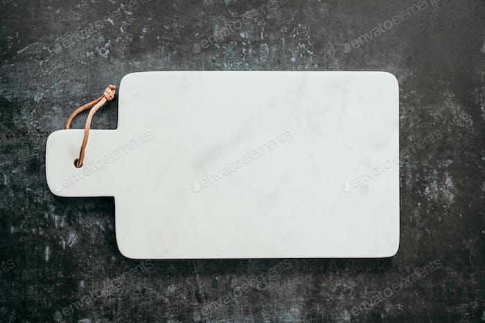 Top down view on an empty white marble cutting board.