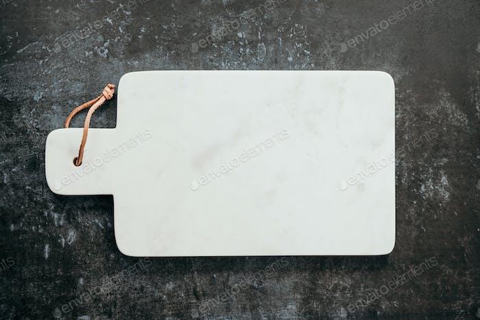 Draufsicht auf ein leeres Schneidebrett aus weißem Marmor.