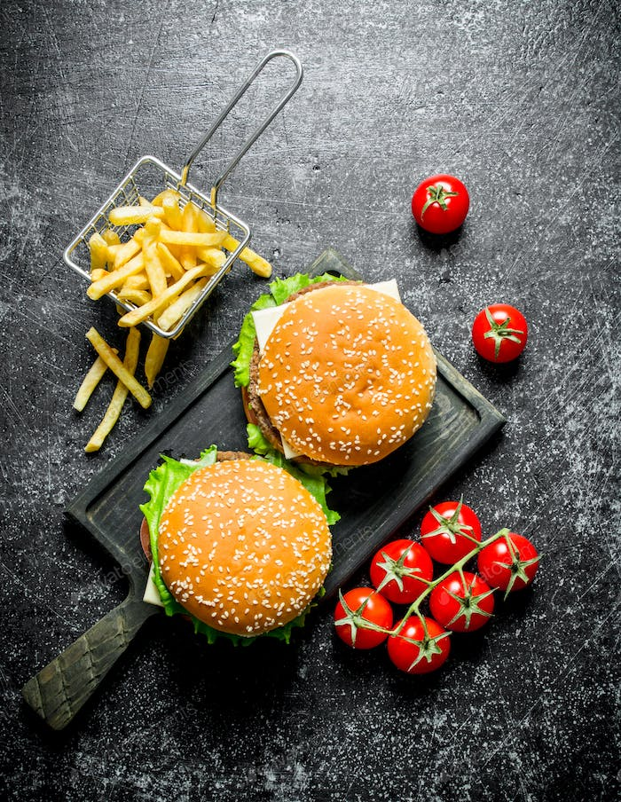 Burgers with fries and tomatoes.