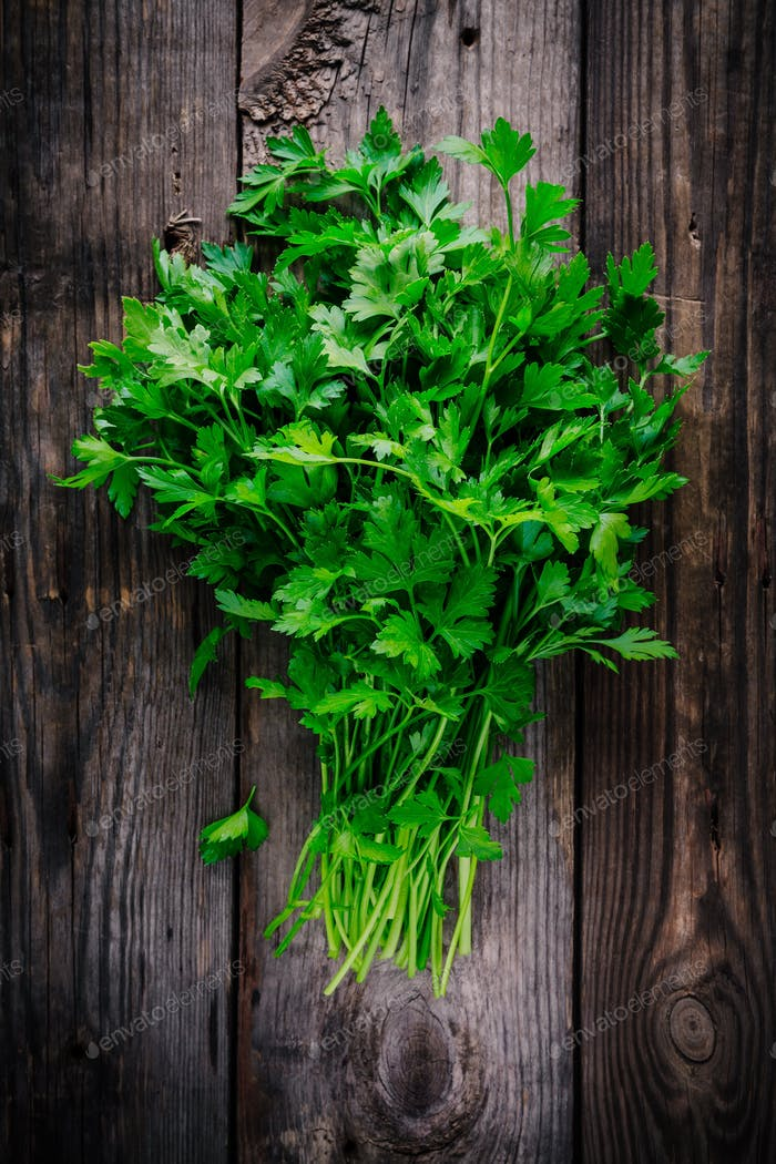 bunch of fresh organic parsley on a wooden rustic background.