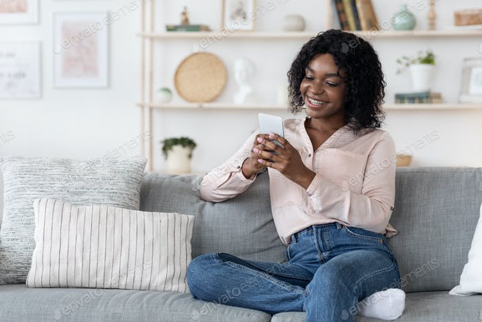 Cheerful black woman relaxing on couch in living room with cellphone