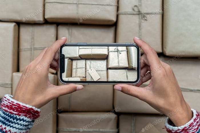 Woman taking a picture of stacked Christmas Presents wrapped in craft paper