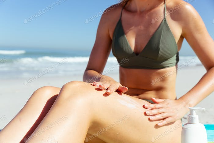 Mid section of woman applying sunscreen at the beach