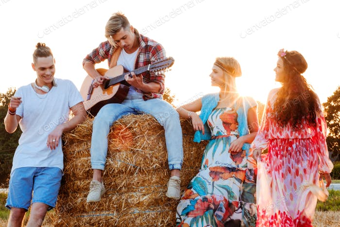 Hippie friends with guitar in a wheat field