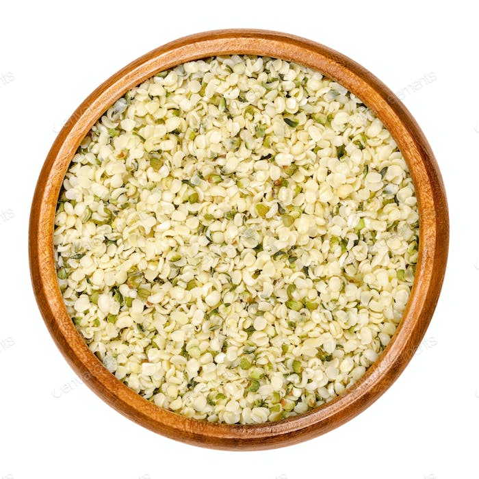 Hulled hemp seeds in wooden bowl over white