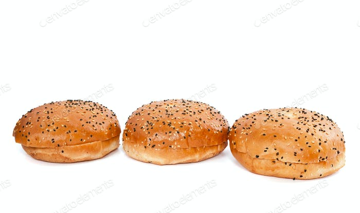 Three burger buns with sesame seeds on white background