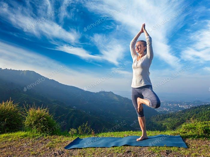 Frau im Yoga Vrikshasana Baum Pose im Freien