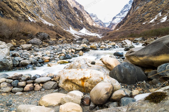 Picturesque valley with river and mountains with melting snow during spring