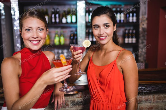Female friends enjoying cocktail at counter in nightclub