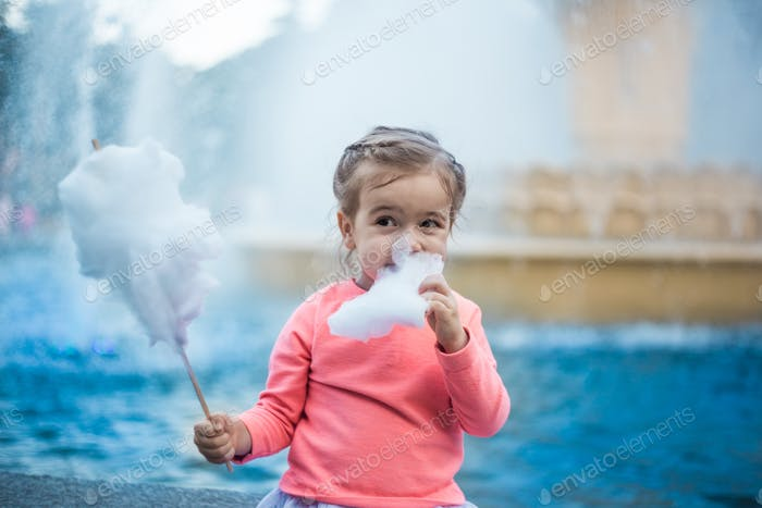 little girl with cotton candy near the fountain