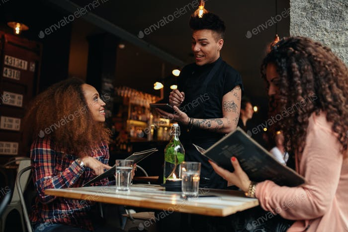 Woman in a cafe ordering to waiter