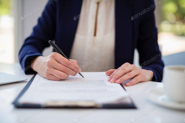 Businesswoman writing on clipboard