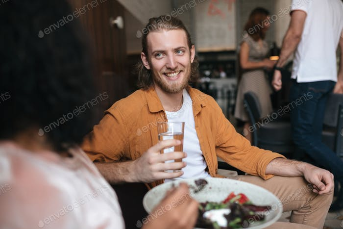 Smiling man sitting in restaurant and talking with girl