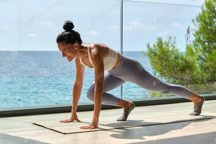 Slim sportswoman training on terrace against ocean in sunlight