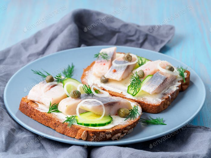 Herring smorrebrod - traditional Danish sandwiches. Black rye bread with herring on dark blue