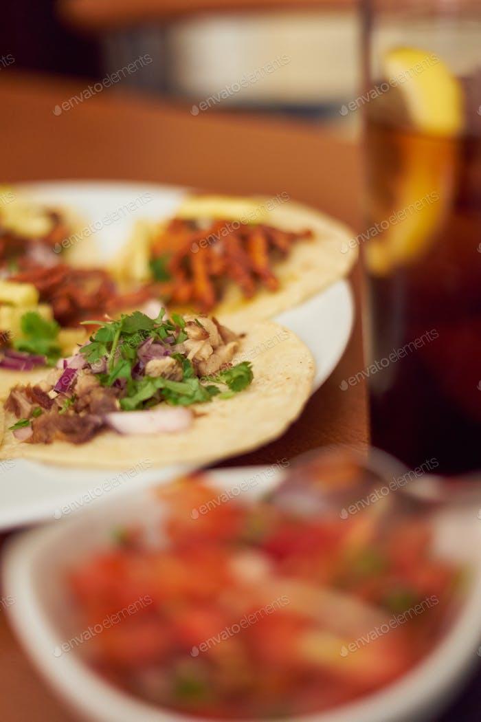 """Mexikanische Tacos """"Pastor"""" und """"Carnitas"""" mit Schweinefleisch und Rindfleisch in gelber Tortilla"""