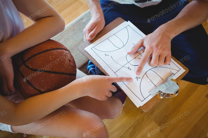 Close up of coach explaining diagram to female basketball player