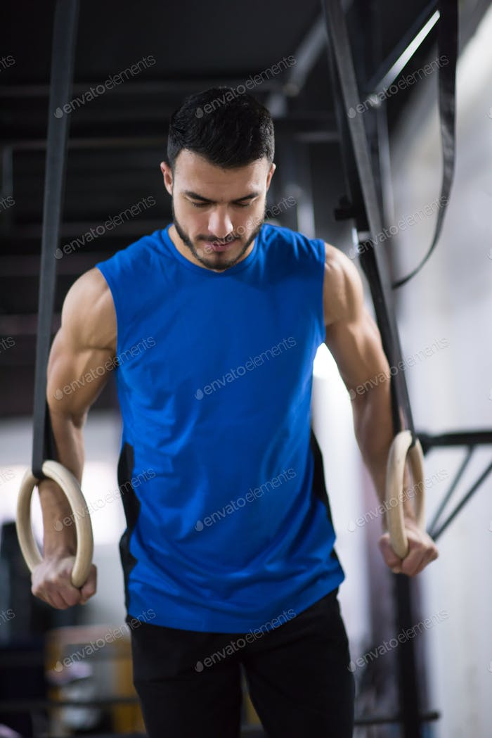 man working out pull ups with gymnastic rings