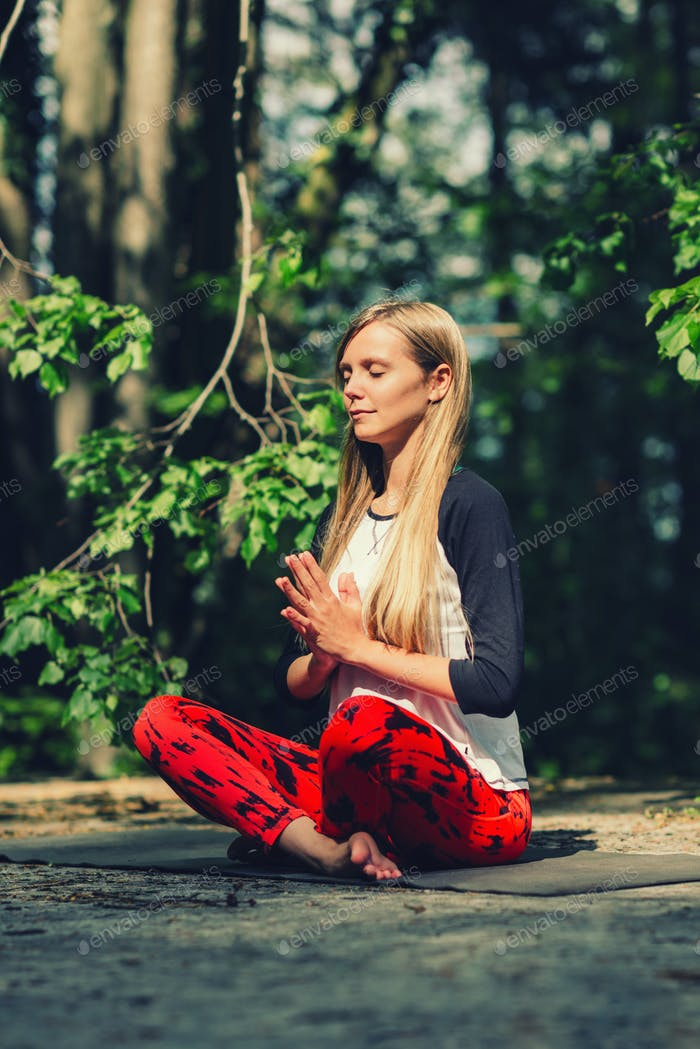 Meditation. Positive young woman meditating outdoors