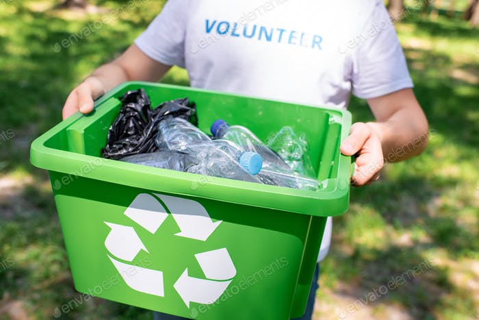 cropped view of volunteer holding recycling box with plastic trash