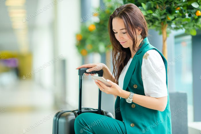 Portrait of young woman with smartphone in international airport. Airline passenger in an airport