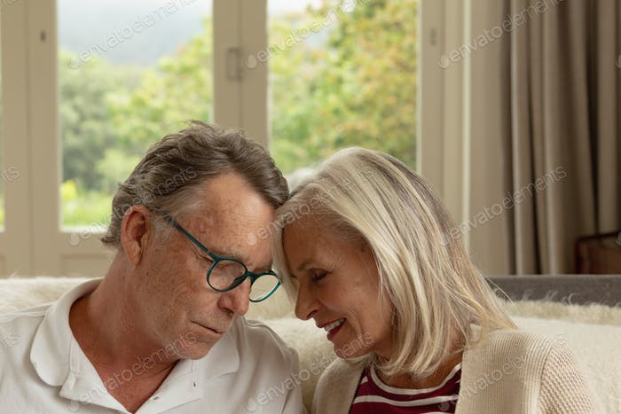 Front view of romantic active senior Caucasian couple head to head on sofa in a comfortable home