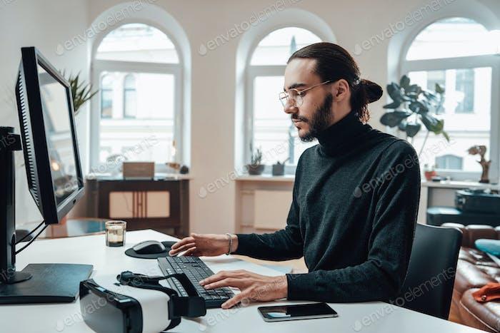 Бородатый офисный работник с длинными волосками на клавиатуре в офисе