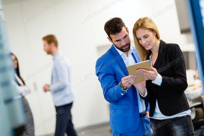 Attraktives Geschäftspaar mit Tablet in ihrem Unternehmen