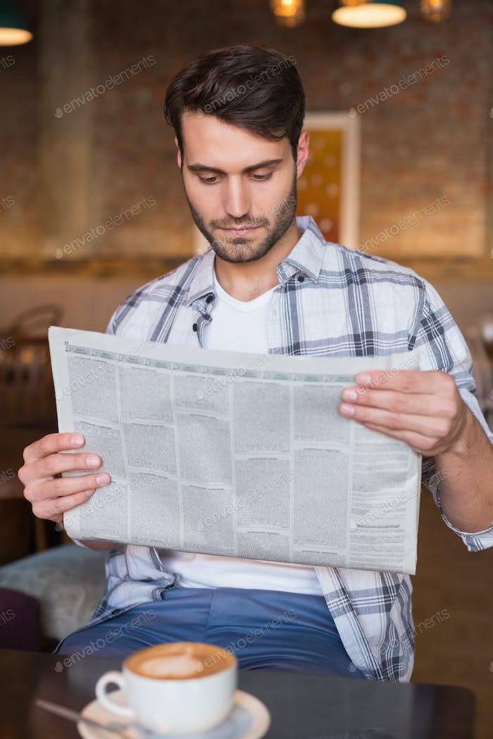 Young man having cup of coffee reading newspaper at the cafe