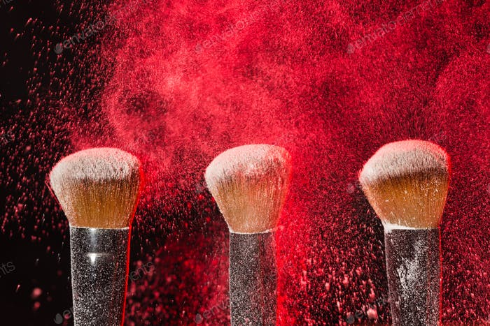 Cosmetics brush and explosion red colorful makeup powder black background