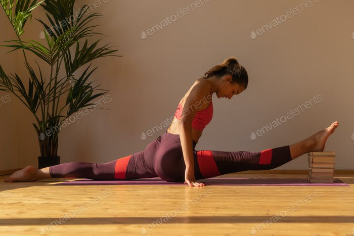 young athletic female doing stretching exercise near window at home