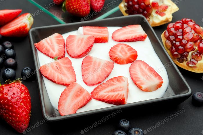 yogurt with fresh fruit on modern black wooden table