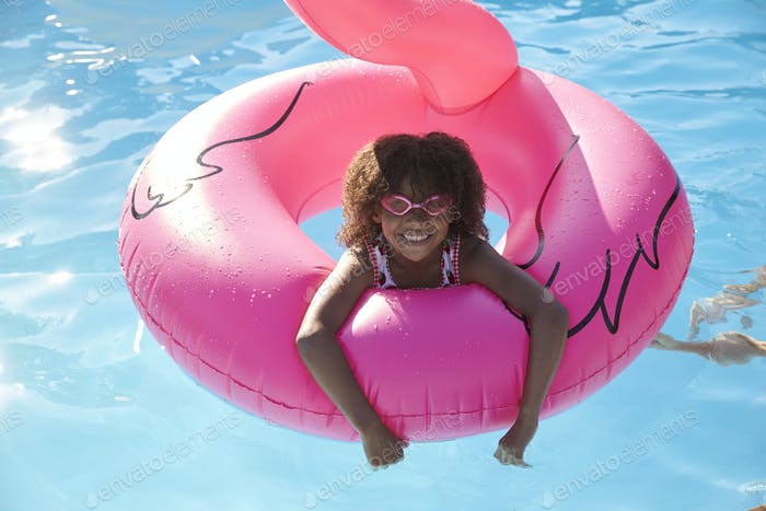 Girl Having Fun With Inflatable In Outdoor Swimming Pool