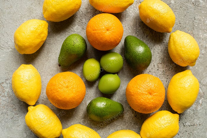 Top View of Colorful Oranges, Avocado, Limes And Lemons Arranged in Circle on Grey Concrete Surface