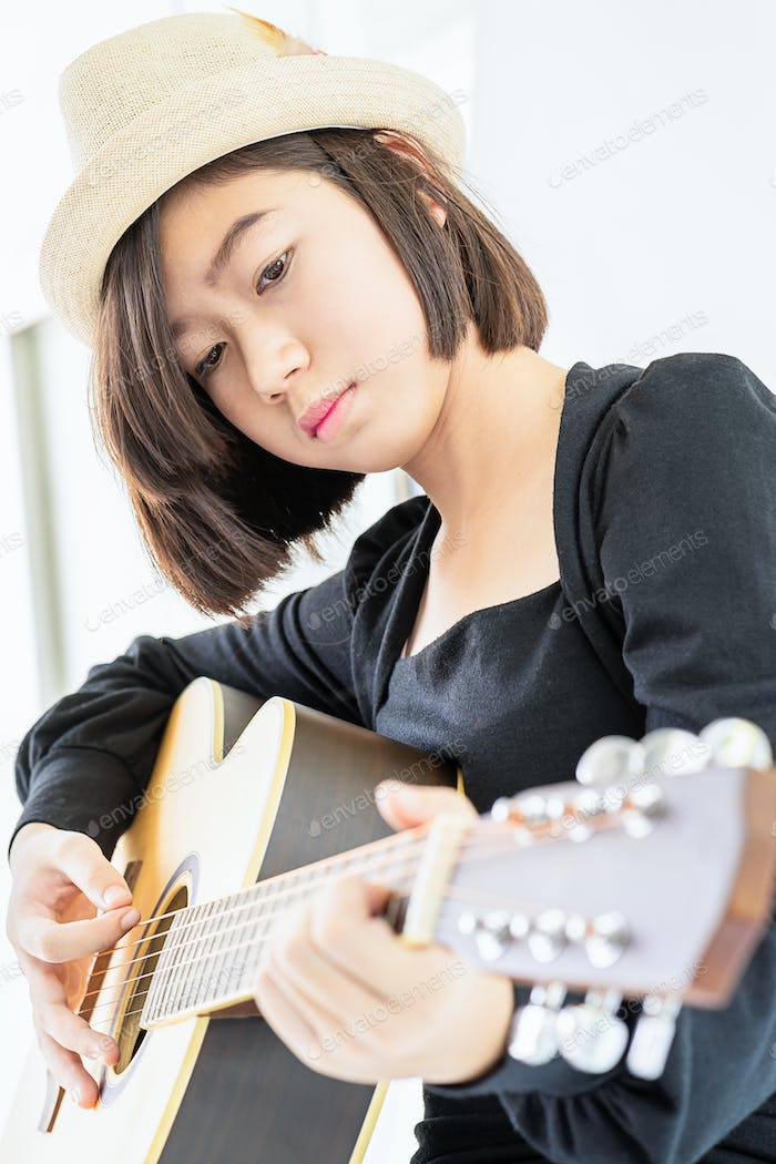 Close up woman playing guitar_