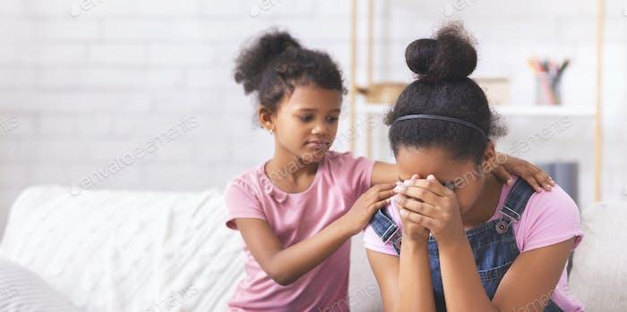Pequeño afroamericano niña consolando su llanto hermana mayor