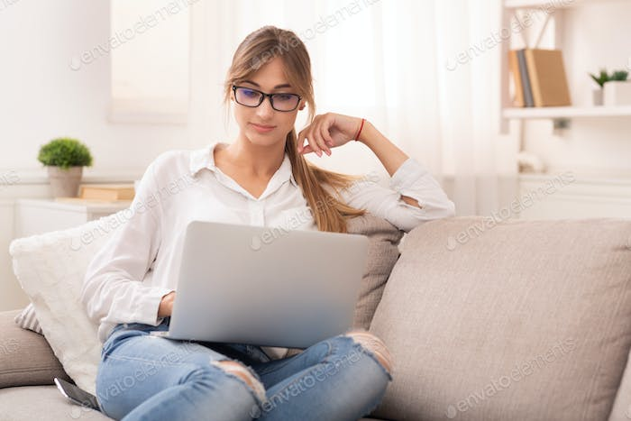 Student Girl Using Laptop Watching Masterclass Sitting On Couch Indoor