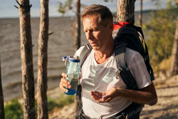 Man quenching thirst while hiking in nature
