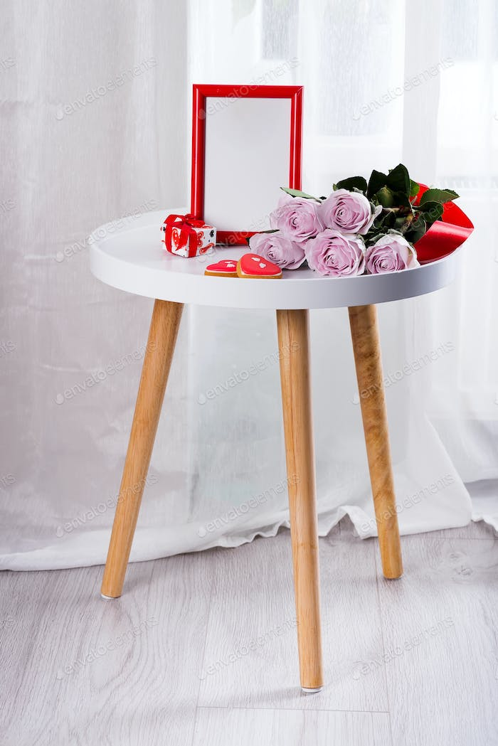 Homemade Valentines day heart cookies, pink roses and red frame on white table near floor, copy