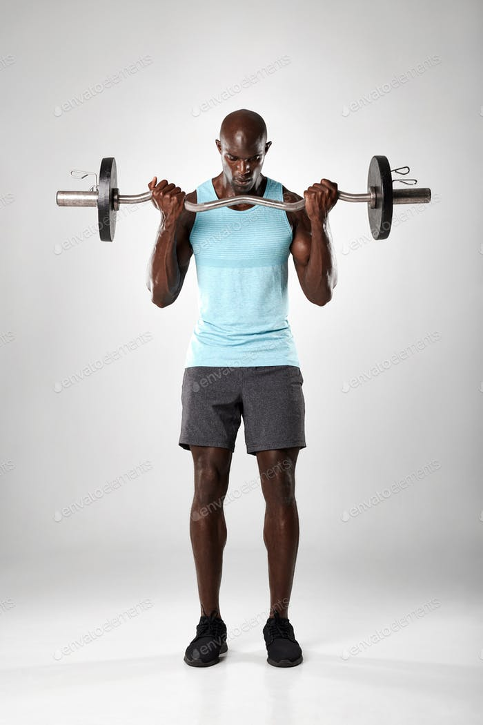 Muscular man exercising with barbell