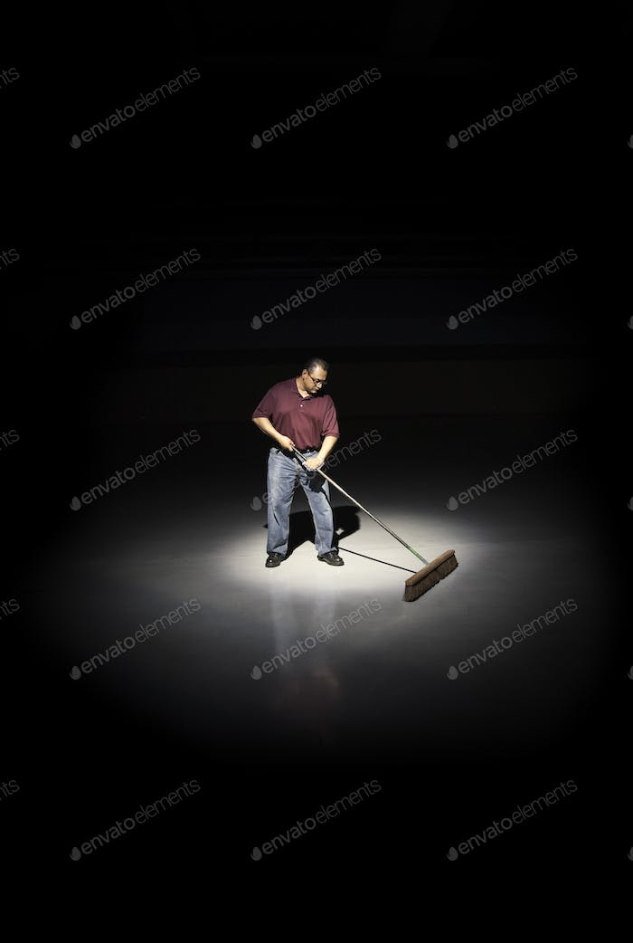 A man with a broom working in an area of a floor lit up by a spotlight.