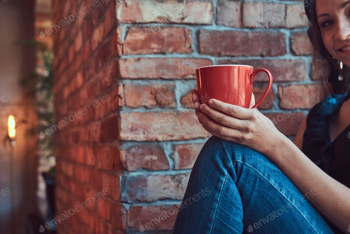 Brunette female listening music in headphones and holds a cup of takeaway coffee