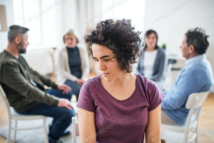 A portrait of young depressed woman during group therapy.
