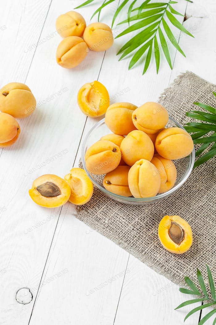 Fresh apricots in a round glass pial on a white board table.